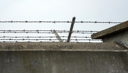 Dreary, soulless concrete wall with barbed wire.
