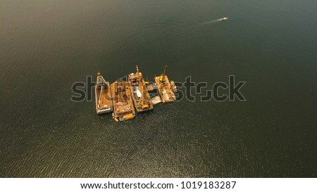 Dredge ship presumably performing harbor and channel maintenance. Aerial view: Huge crane barge Industrial ship that digs sand marine dredging digging sea bottom. Manila, Philippines.