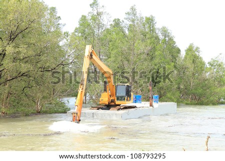 Dredging the canal, Backhoe in the pontoon, working in the canal