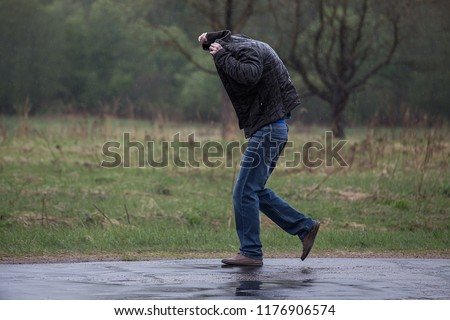 drenched passer-by without umbrella runs in the rain on the road, cold water pours from the sky, unpleasant sensations, cover your head with clothes without a hood