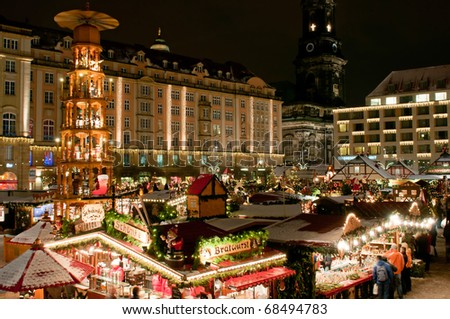 DRESDEN, GERMANY - DEC 20: Tourists enjoy Christmas market on December 20, 2010 in Dresden. One of the highlights is eight meter high Christmas pyramid with the life size hand made wooden figures.