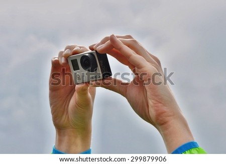 DRESDEN, GERMANY, 27.05.2015: woman holds over head sport camera Go Pro Hero 3 used in extreme situations,
