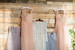 Dress for the bride and her bridesmaids hanging on hangers waiting in wedding ceremony
