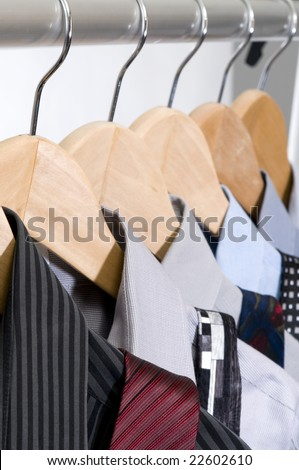 Dress shirts and ties on wooden hangers. - stock photo