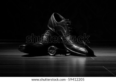Dress shoes and a watch in the spotlight