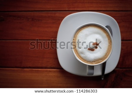 dress up of cappuccino coffee in white cup on brown wood background