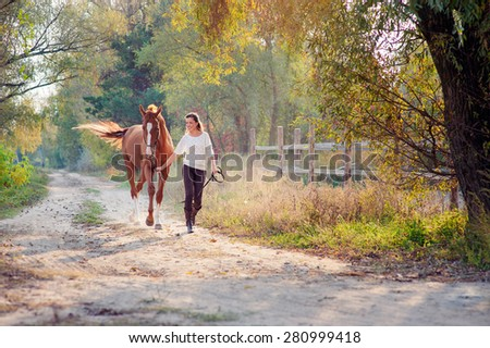 Dressage. Beautiful young woman running with her brown horse at countryside. #280999418