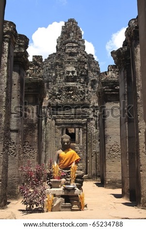 Dressed Bayon Buddhist statue with incense offerings