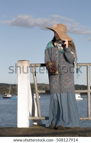 Dressed in blue, wool, vintage clothing, and hiding in the shadows of a straw hat a teenage girl stands on a pier looking into the harbor while the morning sunshine keeps her warm. Vertical format.