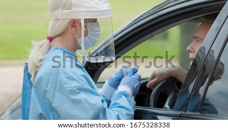 Dressed in full protective gear a healthcare worker collects a sample from a mature man sitting inside his car as part of the operations of a coronavirus mobile testing unit.