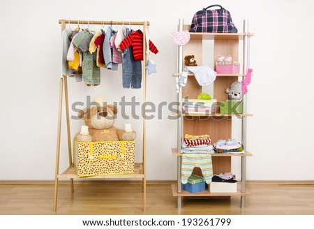 Dressing closet with complementary clothes arranged on hangers.Wardrobe of newborn kids babies full of all shades of blue an orange clothes shoes accessories and toys