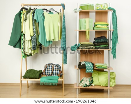 Dressing closet with green clothes arranged on hangers and shelf. Wardrobe full of all shades of green clothes and accessories.