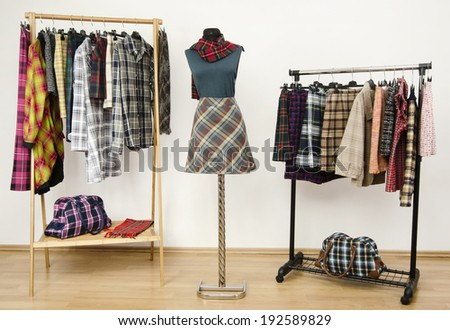 Dressing closet with plaid clothes arranged on hangers and an outfit on a mannequin. Colorful wardrobe with tartan clothes and accessories.