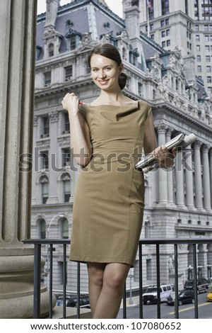 Dressing formally a professional woman is holding stationery, smilingly looking at you and  standing in a business district/Portrait of a professional woman