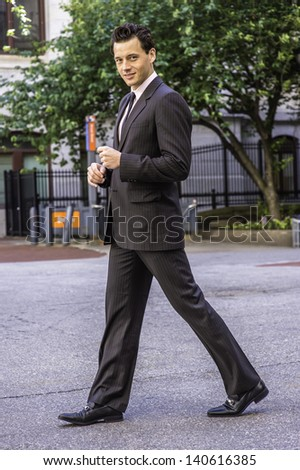 Dressing formally a young businessman is smilingly looking at you and walking away.