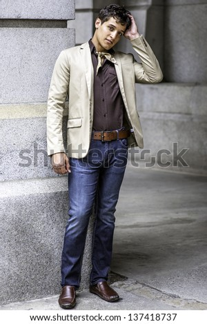 Dressing in a beige color blazer, a coffee color shirt, blue jeans, a scarf tied in the neck,  and one hand touching his head, a handsome guy is charmingly looking at you/Portrait of Young Guy