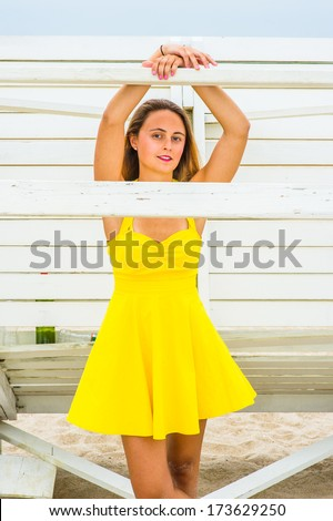 stock-photo-dressing-in-a-bright-yellow-sundress-raising-two-arms-and-hands-resting-on-a-wooden-stick-a-173629250.jpg