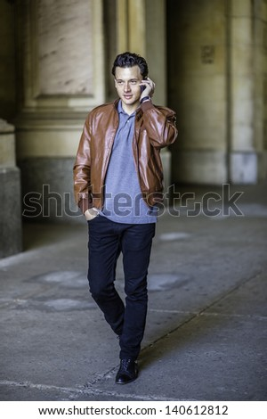 Dressing in a brown leather jacket, black pants and one hand putting in a pocket, a young handsome guy is confidently walking in a hallway and talking on the phone./Talking on Phone