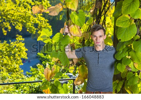 stock-photo-dressing-in-a-gray-long-sleeves-with-roll-tab-henley-shirt-a-young-handsome-guy-is-standing-by-166048883.jpg