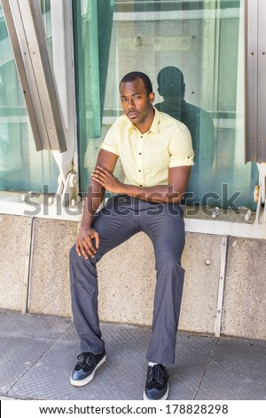 stock-photo-dressing-in-a-light-yellow-shirt-gray-pants-sneakers-a-young-attractive-black-guy-is-sitting-by-178828298.jpg