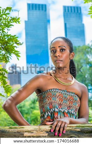 stock-photo-dressing-in-a-strapless-colorful-dress-wearing-a-golden-neck-ring-a-pretty-black-woman-is-174016688.jpg