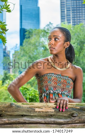 stock-photo-dressing-in-a-strapless-colorful-dress-wearing-a-golden-neck-ring-a-pretty-black-woman-is-174017249.jpg