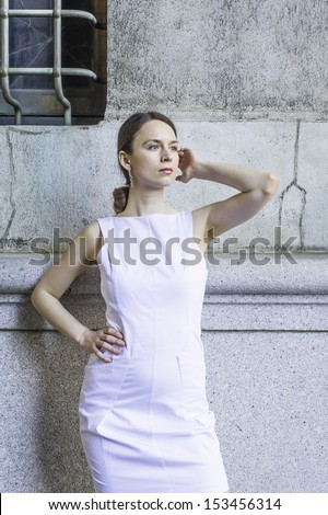 Dressing in a white sleeveless work clothes, a businesswoman is standing outside to take a break. / Take a Break