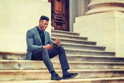 Dressing in fashionable jacket, necktie, pants, cloth shoes, a young black businessman sitting on stairs outside vintage style office building, smiling, checking messages on his cell phone. Texting.