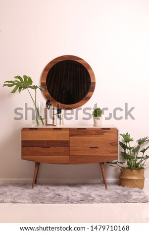 Dressing table isolated with circular mirror frame decorated with plants and carpets. Modern contemporary natural wood furniture vanity table with drawers and wooden legs. Dresser make up table.