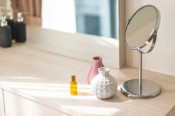 Dressing table with circle mirror, small flower vase in glossy ceramic white and pink vase and reagent bottle on the wooden counter for everyday skin care and cosmetic.