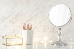 Dressing table with mirror on marble background.