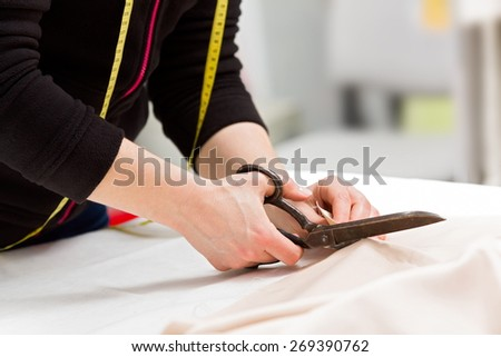 Dressmaker cutting fabric with big old steel scissors