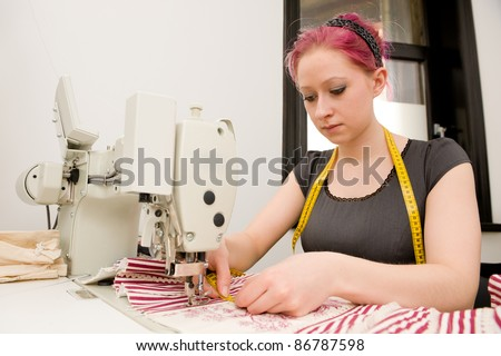 Dressmaker with sewing machine in her studio - stock photo