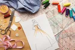 Dressmaking and fashion collection background. Drawn sketches, sewing patterns and various designer accessories on messy table, top view. Creativity concept