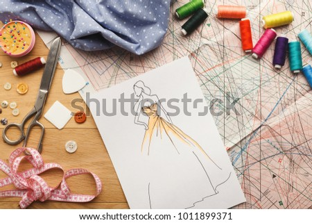 Dressmaking and fashion collection background. Drawn sketches, sewing patterns and various designer accessories on messy table, top view. Creativity concept #1011899371