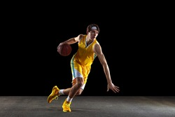 Dribbling. Young Caucasian basketball player, basketballer in yellow uniform training isolated on black dark background. Concept of active life, team game, energy, sport. Copy space for ad, design