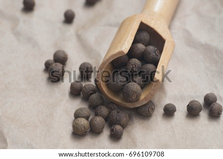 dried allspice  in measuring spoon on paper background #696109708