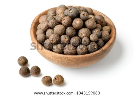 dried allspice in the wooden plate, isolated on white background #1043159080