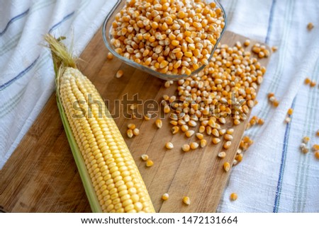 Dried and raw corn on the wooden board together. Raw corn overflowing from bowl. Raw corn seeds, corn kernels, corncob.