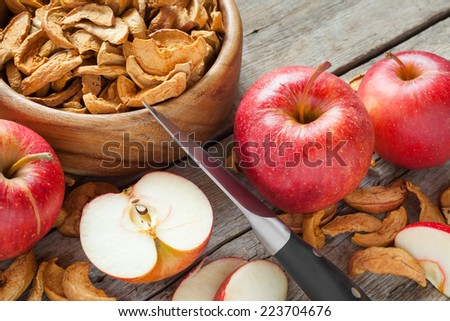 dried apple slices and fresh apple fruit on kitchen table