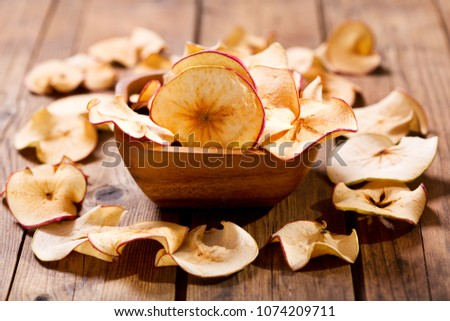 dried apples in a bowl on wooden table