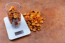 Dried apples in a transparent measuring cup weighed on white electronic weighing The weight of 500 ml of the product is 82 grams. Part of the product is located on the desktop next to the scales.