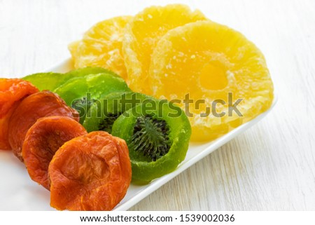 Dried apricots, dried slices of kiwi and pineapple lie on a white glass rectangular dish on a white wooden background, side view from above, close-up