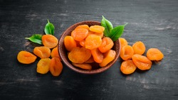 Dried apricots in a bowl on a black background. Top view. Free space for your text.