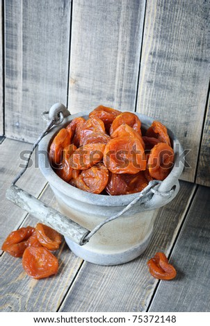 Dried apricots in a bucket on a wooden background
