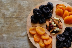 Dried apricots, prunes and nut mix at weathered wooden background