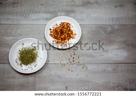 Dried basil and dried red pepper flakes each in a bowl on a wooden background