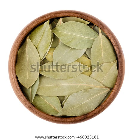 Dried bay leaves in a bowl on white.  Aromatic leaves of Laurus nobilis, also called laurel, used for seasoning in cooking. Edible, raw and organic food. Isolated close up macro photo.