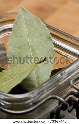 Dried bay leaves with jar on wooden board