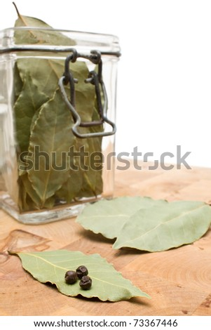 Dried bay leaves with jar on wooden board - stock photo